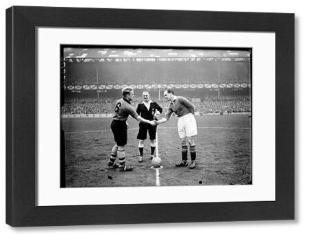 Referee JH Parker (c) looks on as Wolves' captain Billy Wright (l) shakes hands with Manchester United captain Johnny Carey (r)