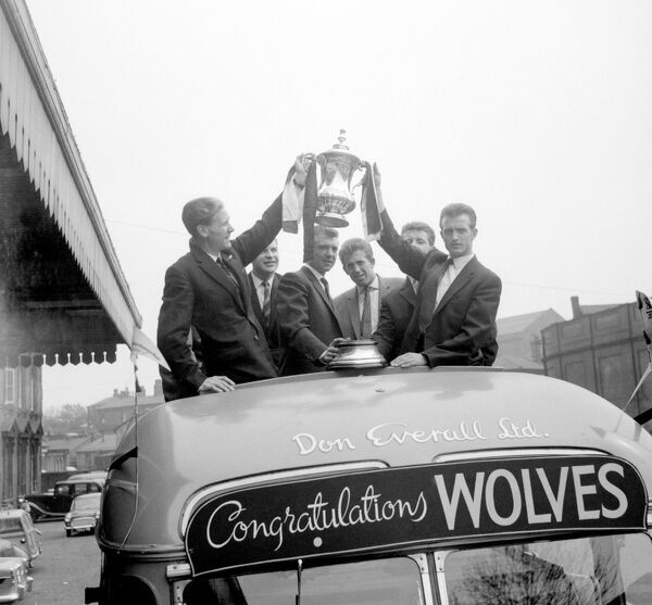 Wolverhampton Wanderers' Bill Slater (l) and Gerry Harris (r) show off the FA Cup as the team begins an open-topped bus tour of Wolverhampton, the day after their 3-0 win over Blackburn Rovers