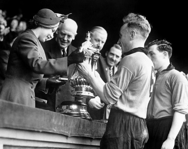 Princess Elizabeth presents the Football Association Cup to Billy Wright, captain of Wolves' after they defeated Leicester City by three goals to one in the final at Wembley Stadium