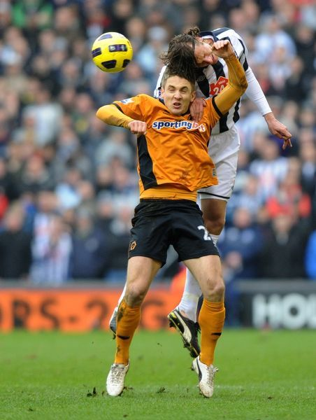 Kevin Doyle of Wolverhampton Wanderers and Jonas Olsson of West Bromwich Albion